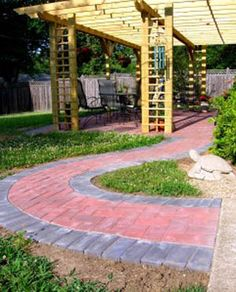 Colorful Holland pavers give flair to this curving walkway and encourage…