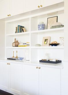 Chic living room features white built in shelves sandwiched between white cabinets adorned with ...