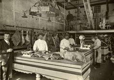 Interieur van een grote Amsterdamse slagerij met grote stukken vlees / karkassen aan haken en op de slachtbank. Links de eigenaar in net pak...