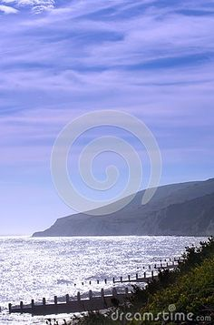 A view of Beachy Head seen from the shore of Eastbourne with a sparkling sea.