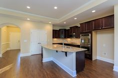 Kitchen with island, staggered cabinets, granite countertops and stainless steel appliances in the Salerno
