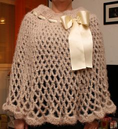 Airy poncho with glitter yarn and a ribbon for decoration.