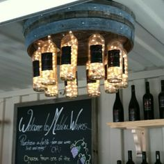 Chandelier made with a wine barrel, empty wine bottles and strands of Christmas…