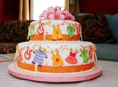 Cute baby shower cake with baby clothes on a line.