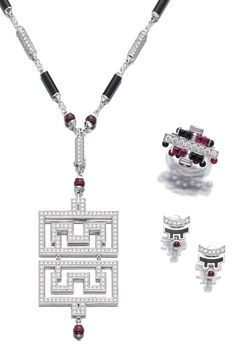RUBY, ONYX, LACQUER AND DIAMOND PARURE, 'BAISER DU DRAGON', CARTIER.  Comprising: a necklace set with polished onyx, ruby beads and brilliant-cut diamonds, suspending a detachable pendant; a bracelet of similar design set with buff top and cabochon rubies and onyx; a ring en suite and a pair of earrings similarly set with black lacquer, post and hinged back fittings; each signed Cartier. [Bracelet not illustrated]