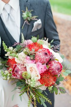 Loved it! Pinned it! A Blooming Envy Design! Photo by Ashlea Snell Photography. Bouquet designed with Pin Cushion Protea, Pink Ice Protea, Blush Garden Roses, Blush Snapdragons, Limonium, Succulents, Eucalyptus and Grevillea. Boutonniere made with Succulents, Grevillea and Limonium.