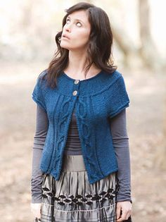 Loppem is a yoked cardigan. The cap raglan sleeves are simply an extension of the yoke that buttons at the neck. The cardi swings open with an easy cable banding the center front edges.