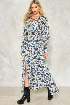 Snatch it up on floral grounds. The Julianna Dress features a vibrant floral print, full maxi silhouette, long sleeves, two front slits, and subtle lace-up detailing at chest..