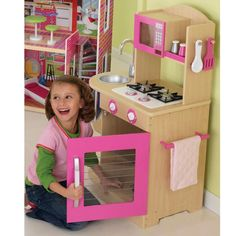 """With bright pink accents and smart, sturdy construction, the KidKraft Pink Wooden Play Kitchen will keep your little chef busy for hours. Complete with stove, oven, microwave, sink and starter accessory set, the play kitchen is sure to encourage interactive play and imagination. The pink wooden playkitchen has enough room for the head chef and assistants with room to spare. There's no limit to the number of """"feasts"""" your little one will dream up in their ve..."""