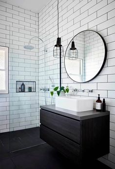 Bathroom White subway tiles are laid horizontally in this smaller bathroom, with the same large format black tiles on the floor. A circular mirror sits above a white basin and black timber vanity, with an industrial-style pendant lamp hangs above. Bad Inspiration, Bathroom Inspiration, Bathroom Design Small, Bathroom Interior Design, Interior Paint, Bathroom Renos, Bathroom Flooring, Basement Bathroom, Bathroom Renovations