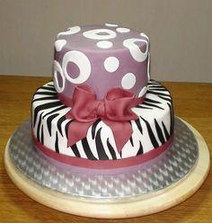 Gâteau d'anniversaire Girl Friendly Il s'agit ici d'un gâteau d'anniversaire qui se compose d'un fraisier : d'un Victoria's sponge cake, de trois couches de crème pâtissière et des morceaux de fraises. L'imprimé zébré, les motifs, les rubans et le noeud...