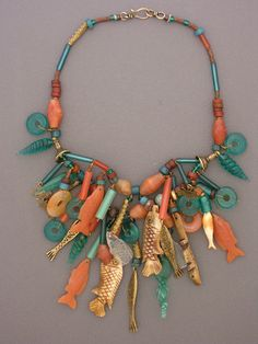Necklace | Anna Holland ~Dorje Designs. A fun collection of bone, bronze, and carnelian fish pendants which Anna has brought together from all over the world.  These have been combined with an assortment of glass and carnelian beads and bronze  charms