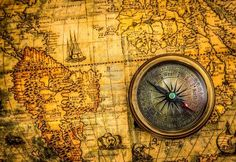 Vintage compass lies on an ancient world map of 1565.