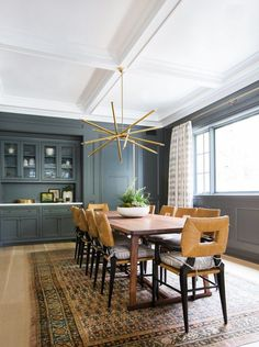 Dunn Edwards paint in Cavernous highlights the formal dining room's elegant paneling | archdigest.com