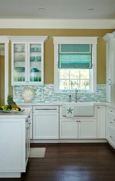 Beautiful white kitchen with light turquoise/green backsplash #BarbsBeachHouse