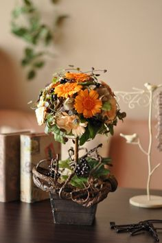 プリザーブドフラワーのアレンジメント。オレンジのグラデーションが鮮やかなガーベラのトピアリーです。  木製の花器でナチュラル感あふれるアレンジになっています。