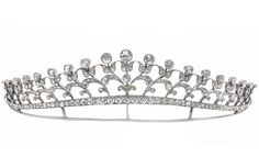 A colourless paste spray tiara, circa 1900.  Designed as a tapering spray of stylized flowers, collet-set throughout with circular-cut colourless paste, to a demilune-shaped tapered border of similarly-cut colourless paste, above a conforming mount, three paste deficient, width 15.2cm, cased