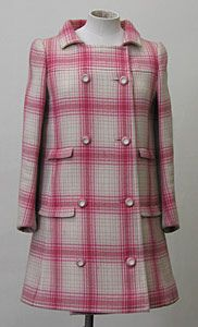 Heavy-weight Shetland wool coat by Emanual Ungaro, French, c. 1960's. The fabric is backed with a cream pilled wool interlining to give a more solid appearance. The coat is yoked above the bust and has a two-piece sleeve. It is double-breasted fastening with four pink and cream plastic buttons, and bound button-holes, and is mini-length. The collar has a gap of 10 cms in the front. There are four pocket flaps but no pockets, two either side of the front on waist line and hips. The back also…