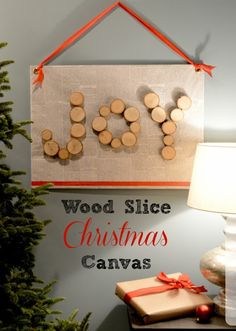 DIY Wood Slice Christmas Canvas - A simple home decor craft to make for Christmas. Use wrapping paper or recycle old newspaper and decoupage it onto the canvas.
