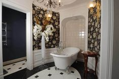 This is a chic bathroom that has walls adorned with floral wallpaper in between white molding and wainscoting contrasted by the black details of the tiled floors. Master Bathroom, Bathroom Wall Tile, Chic Bathrooms, Elegant Bathroom, Bathroom Colors, Mold In Bathroom, Bathroom Photos, White Molding, White Master Bathroom