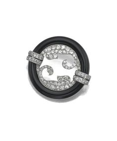 Diamond and onyx circle brooch, Cartier, Paris, circa 1925 - The circle formed of two curved segments of onyx, enclosing scrolls of old European-cut and single-cut diamonds, the terminals with decorated with single-cut diamond bands, mounted in platinum. | © 2015 Sotheby's