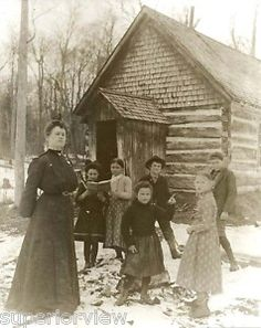 *This photo shows teacher with her students, in front of a rustic, one room schoolhouse in the U.P. of Michigan.