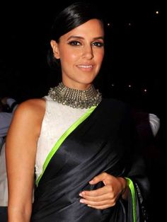 Neha Dhupia: Neha looks elegant in this white sleeveless blouse paired with a black sari that has a neon border. She wore a statement necklace to add a tribal touch to her look.