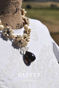 Wonderful handmade necklace, the flowers made with beads pip and mother of pearl ending with a Swarovski pearl e a beautiful pendant in smoky quartz.A jewel elegant and casual at the same time depending on the garment worn.