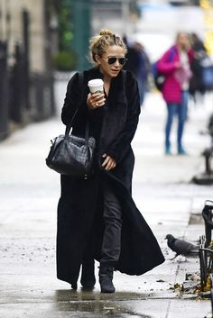 Mary-Kate Olsen wears a floor-length black coat with black pants, suede boots, and a duffle bag