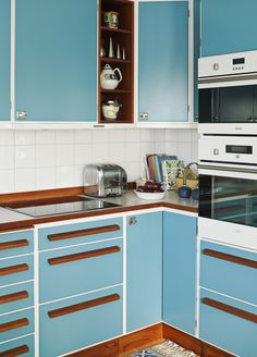 A Retro-inspired contemporary kitchen. The iconic turquoise blue of the MID-CENTURY MODERN contrasted against mid-toned wood color. The white back-on-trend square tiling & white trims around the drawers & overhead cabinets, freshen up the look. 60s Kitchen, Kitchen Interior, Vintage Kitchen, Kitchen Dining, Kitchen Decor, Kitchen Cabinets, Kitchen Slab, Kitchen Ideas, Smart Kitchen
