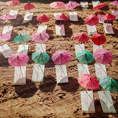 """Brides.com: . To fit the vibe of their Bollywood beach wedding, this couple chose a whimsical escort card display that featured paper """"beach towels"""" and little umbrellas."""