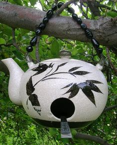 Spruce up your garden or yard with this one of a kind Tea Kettle Birdhouse made of a tea kettle and some old flat ware as a perch. This bird house is hung with wire decorated with glass beads.