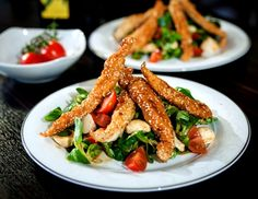 In Sesam gebackene Hühnerstreifen auf Vogerlsalat mit Tomate-Mozzarella