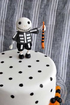 Halloween Cake MD...I could do something like this for a cake to go with cupcakes...not the person on top, you can put a bride and groom on top...but simple white with black dots with black and orange (or your purple!!!!) jellybeans around edge????