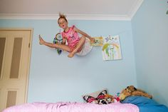 A little girl jumps high on her bed