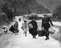 A member of the French frontier troops helps a family of refugees cross the border from Spain, 1938.