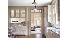 I love transom windows and I like the way this one echoes the openness of the glass cabinets. A nice way to create room division without closing off the room.