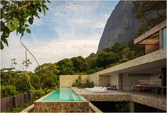 AL HOUSE | BY STUDIO ARTHUR CASAS, Located in Rio de Janeiro, the 5,200-square-foot dream house is set around lush vegetation and over the iconic landscape clinging to a slope of the Pedra da Gavea dome. The house features floor-to-ceiling sliding glass panels that open onto an amazing infinity pool with breathtaking views of the dramatic scenery.  More photos below