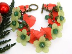 This handmade holiday bracelet is sure to put you in the spirit of the season!  Red and green Lucite flowers and leaves are paired with genuine Swarovski Austrian crystals and dangle from antique bras