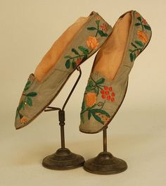 LADYS FLORAL EMBROIDERED SILK SHOES, LATE 18th C. Grey faille flat straights having square toe, the vamp and quarter decorated with red, apricot and green silk satin stitch flowers, silk bengaline binding, lined in shot silk, linen insole.