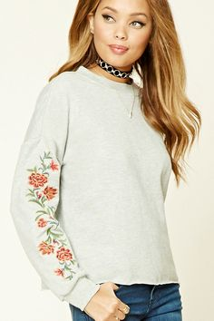 A heathered knit sweatshirt featuring floral embroidered long sleeves, ribbed trim, raw-cut hem, French terry cloth lining, and a round neckline.