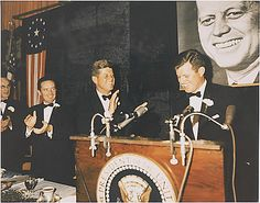 October 19, 1963:   President John F. Kennedy applauds his brother, Sen. Edward Kennedy (D-Mass.), right, during a Democratic fund raising dinner in Boston.