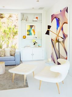 White living space with built-in bookshelf, modern artwork and armchair