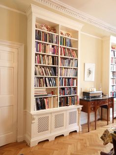 A Verny bespoke bookcase and radiator cover. Build up to staircase molding in front hallway?