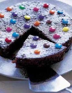 Recette Gateau au chocolat décoré aux smarties : Préchauffez le four th. 6/180 °C. Beurrez et farinez un moule à manqué de 20 cm de diamètre. Faites fo...