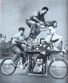 """CARRYING four persons & a sewing machine, the world's weirdest bicycle recently had a tryout in Chicago, Ill. The 2-story vehicle, known as the """"Goofybike,"""" is the creation of Charles Steinlauf. It carries the whole Steinlauf family. The inventor rides at the top & guides the contraption by means of a huge automobile steering wheel. Mrs. Steinlauf sits below, operating a sewing machine, while her son pedals behind & her daughter rides on the handlebars in front."""