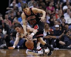 Miami Heat's Mike Miller (L) reaches for a loose ball against Chicago Bulls' Kyle Korver in the first half of their NBA basketball game in Miami, Florida April 19, 2012.