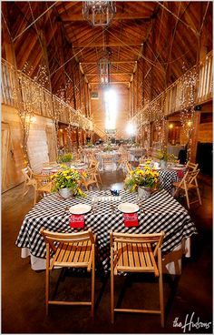 Black-and-white checkered table cloths with potted sunflowers as centerpieces for a rustic barn wedding. I especially love the red bandanas used as napkins! So cute! - Photo by Jason