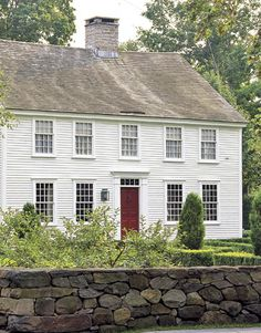 Classic white Colonial, red door, small pane windows, center chimney, granite stone wall.