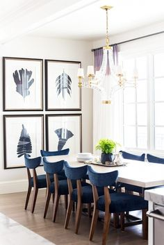 Dining space with a gallery wall, a crystal chandelier, and blue velvet lined armchairs
